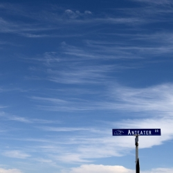 Anteater Drive street sign in bottom corner of photo with beautiful blue sky taking up most of the screen